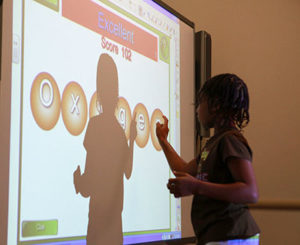 Child playing game on classroom board